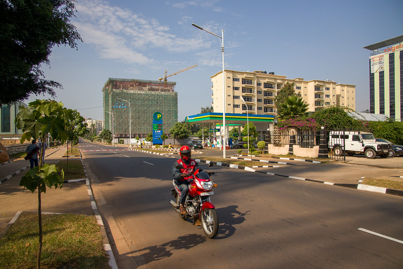 A moto taxi passes a gas station and new construction in Kigali Rwanda