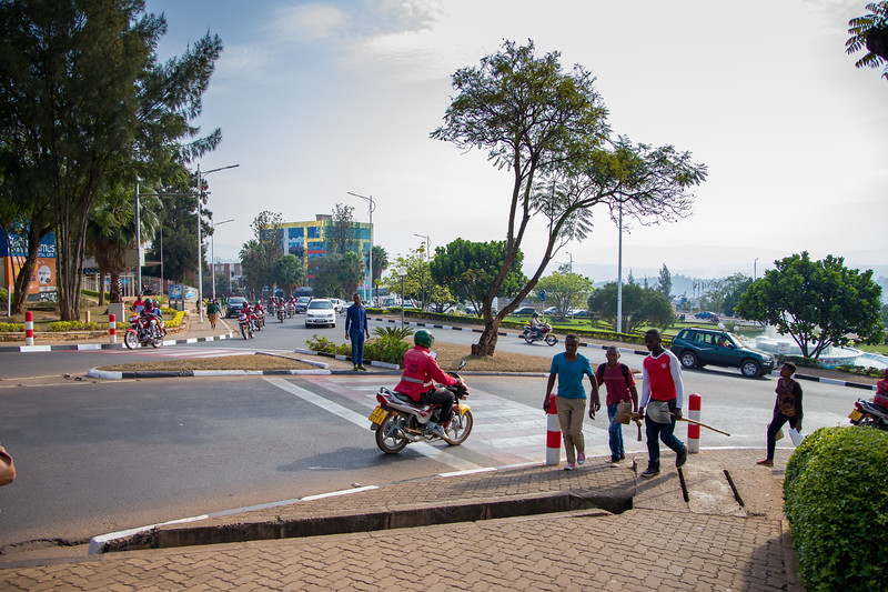 Pedestrians and vehicles in a busy sidewalk scene at a traffic circle in Kigali Rwanda.