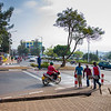 Pedestrians and vehicles in a busy sidewalk scene at a traffic circle in Kigali Rwanda.