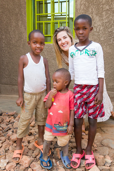 Children pose with Ashley Eure from the PEACE Team outside the home of a widow and victim of the genocide in Kigali Rwanda.
