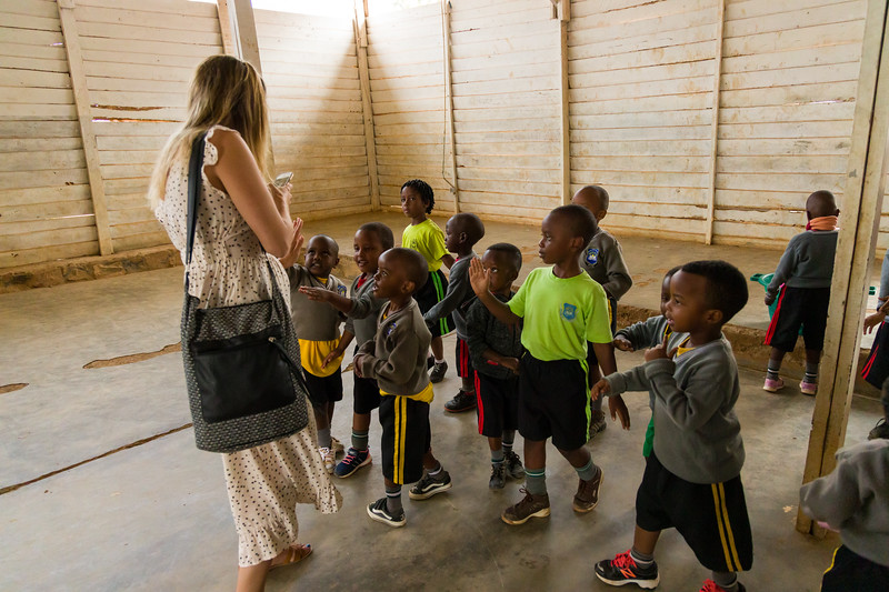 Children greet Ashley Eure during recess time at a PEACE sponsored school in Kigali Rwanda.