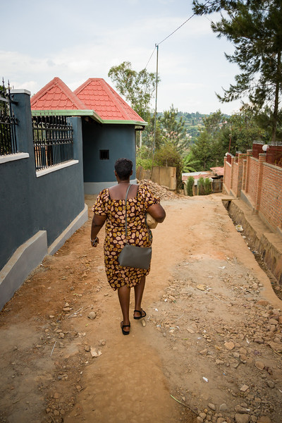 Odethe carries groceries along a dirt road to give to a widow living with HIV in Kigali Rwanda.