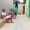 A widow with HIV and victim of the genocide sits on a stoop outside her home in Kigali Rwanda