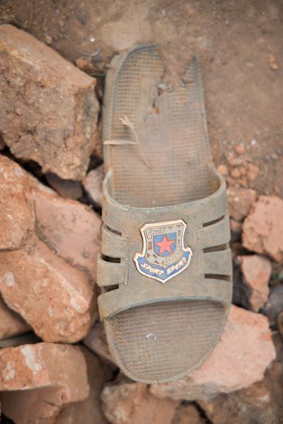 A thoroughly worn-out sandal sits on the rocks outside the home of a widow who is HIV positive and a victim of the genocide in Kigali, Rwanda.