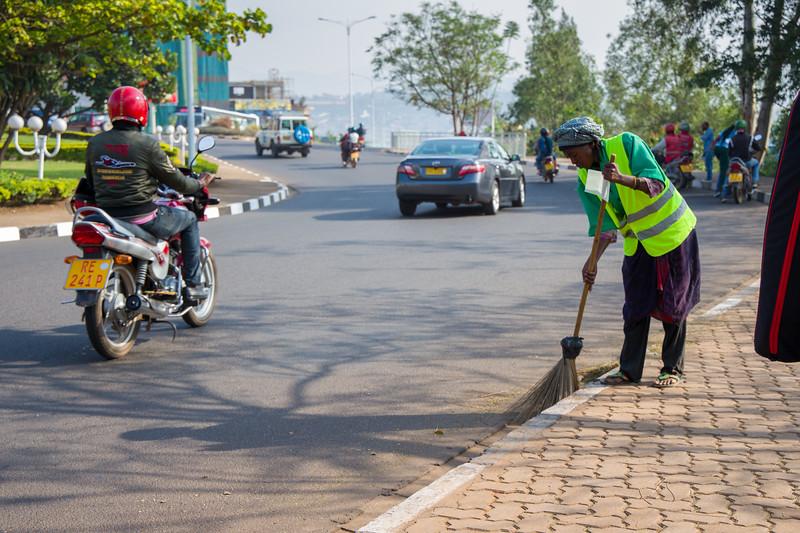 City worker in Kigali Rwanda sweeps the street as traffic passes by.