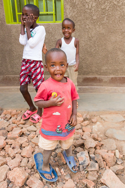 Children smile and laugh outside the home of a widow and victim of the genocide in Kigali Rwanda.