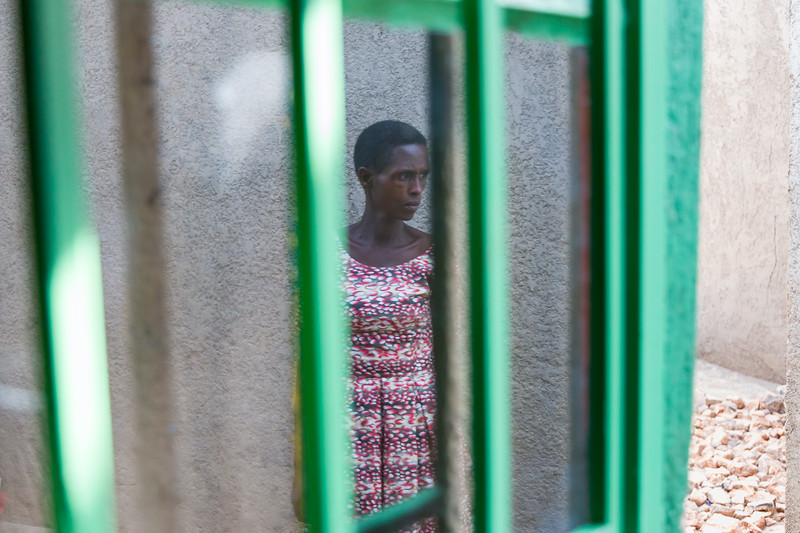 A widow with HIV and victim of the genocide is reflected in a window outside her home in Kigali Rwanda