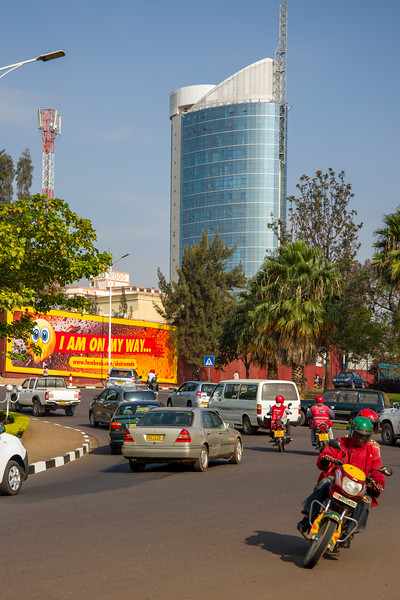 Moto taxi and autos navigate a large traffic circle on a sunny early morning in Kigali Rwanda.