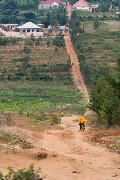 Young men carrying Jerrycans along a steep dirt road in Kigali Rwanda.