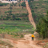 Young men carrying Jerrycans along a steep dirt road in Kigali Rwanda.
