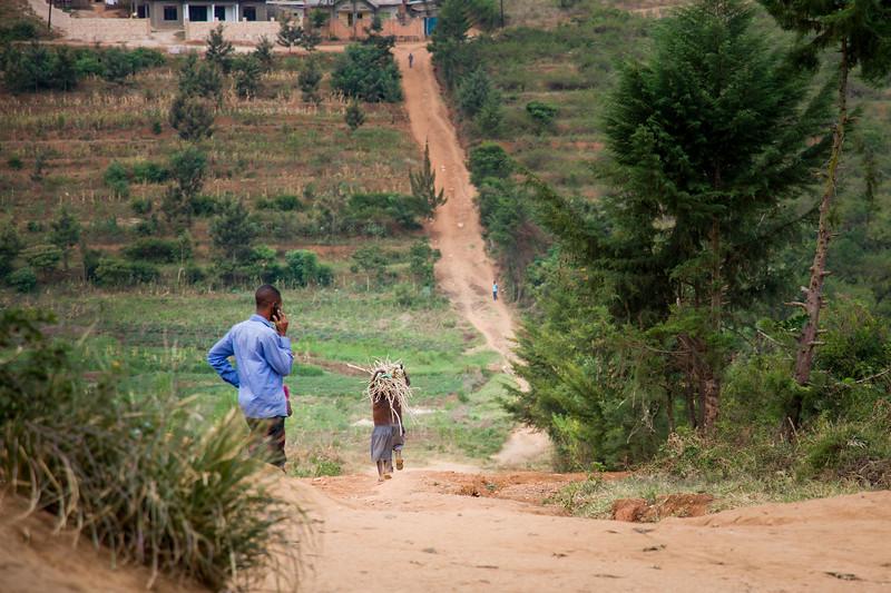 Boys carrying bundles of sticks along a steep dirt road in Kigali Rwanda