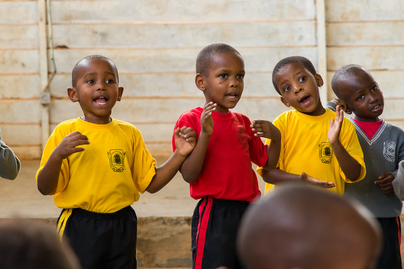 Children and aides sing and dance during recess at a pre-school in Kigali Rwanda.