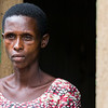 A widow with HIV and victim of the genocide stands in a doorway in Kigali Rwanda