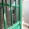 A widow with HIV and victim of the genocide is reflected in a window opposite her daughter who is also HIV positive outside her home in Kigali Rwanda