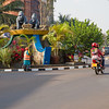 A moto taxi passes in front of a stature in the middle of a traffic circle while a city worker sweeps in Kigali Rwanda.