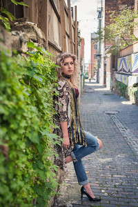 Sarah leaning against wall with greenery