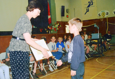 June 1997 Alex presenting his framed picture of a soccer game to the principal. Suncor chose his to be framed. Team 1 (Grades 1&2) presented pictures to be made as postcards for the Police and Fire World Games.