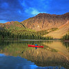 A woman casts to rising trout from her kayak at Alta lake, Colorado