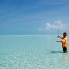 a fly fisherman casting to bonefish in the tropical waters of the exuma islands, bahamas
