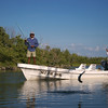 a fly fisherman hooks a jumping Tarpon while fishing from a flats boat off of Isla Holbox Mexico