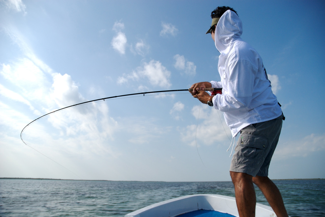 a fly fisherman with a large Tarpon on his line Isla Holbox, Mexico