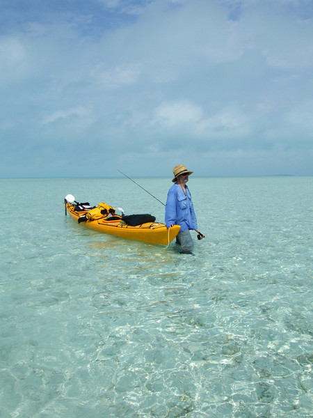 a fly fisherman tows his kayak and walks the flats of the Exuma Islands in search of Bonefish, Bahamas