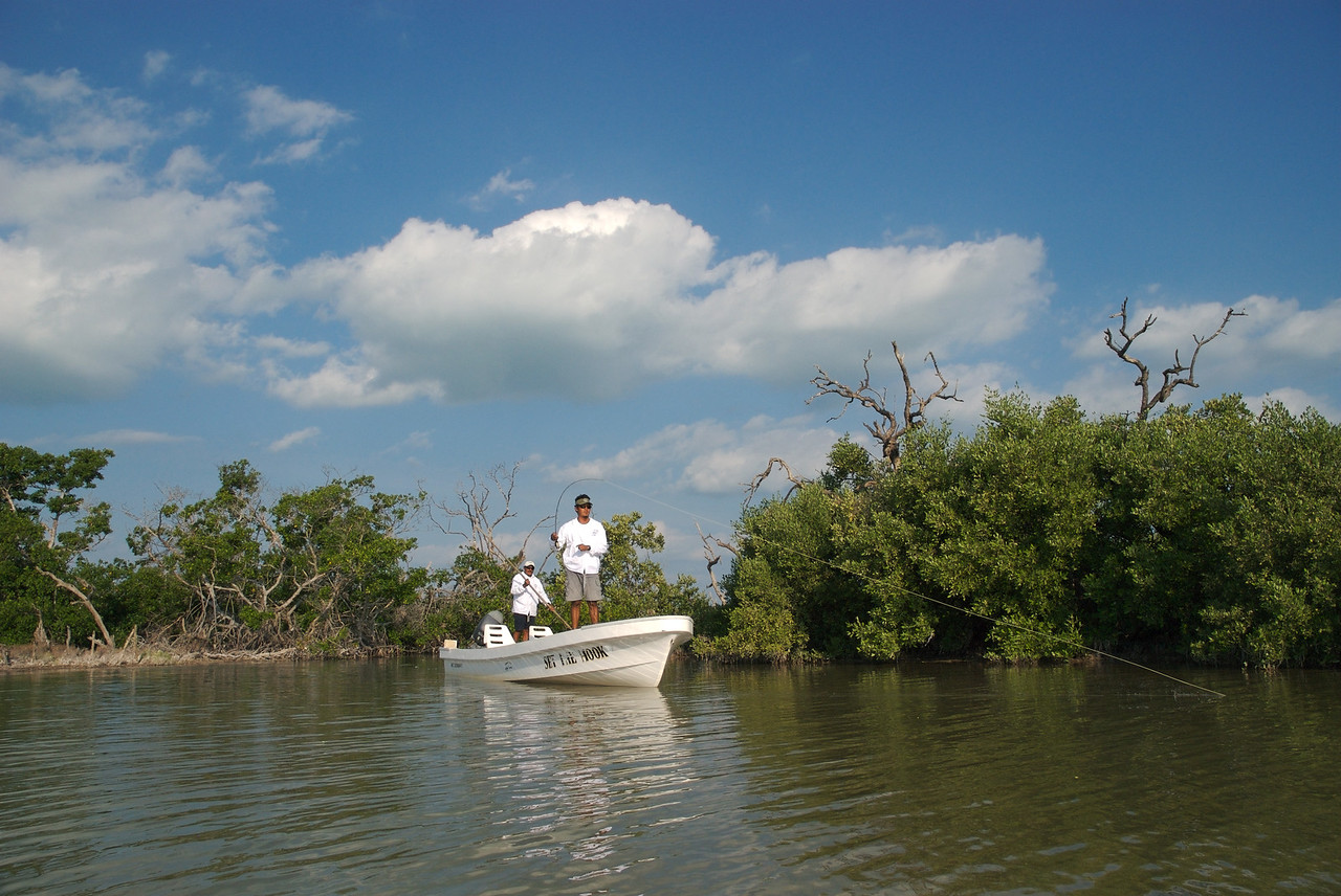 A fly fisherman with a baby Tarpon on his line on Isla Holbox Mexico