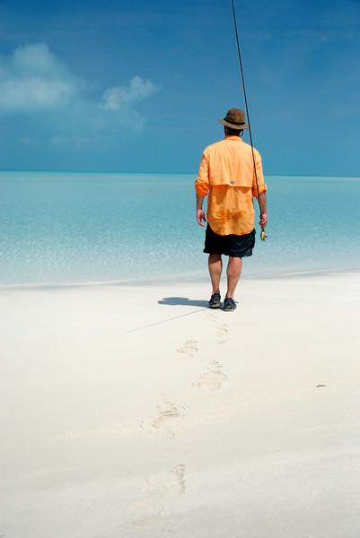 a fly fisherman walking on the beach  to fish the exuma islands flats, bahamas