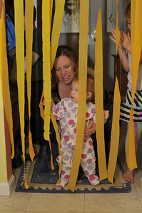 Julie enters the kitchen on her birthday day.  Jenny always works very hard to make sure each child's birthdays are very special and memorable.  The streamers are a trademark of her dedication to this.  Here Julie stops to play with them before going to sit down for breakfast.