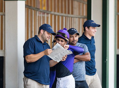 Brad Cox and jockey Shaun Bridgmohan confer before a Claiming Race at Churchill Downs 6.30.18. Brad's assistant, Jorje Abrego, and son Blake are in the background.