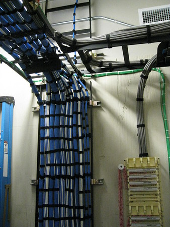 wire dressing into telcom room -- ladder racks on wall and overhead to equipment racks -- all cable are secured with velcro wraps