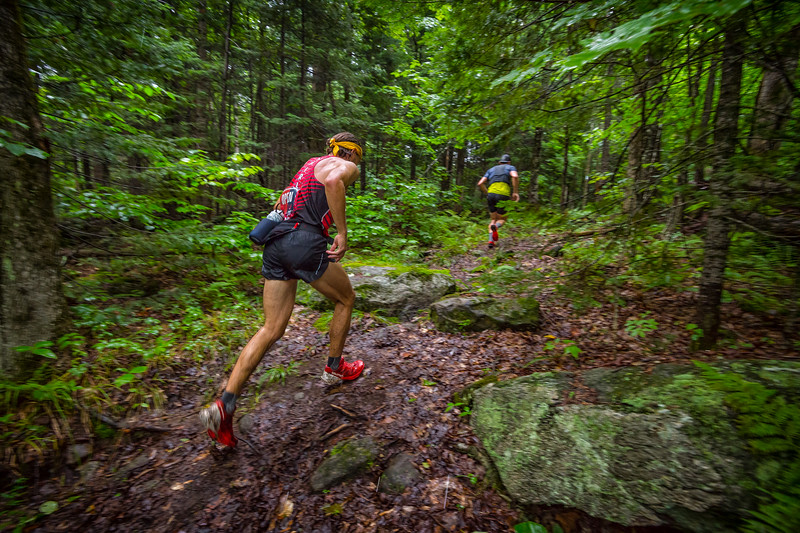 Brandon Newbould chases Simi Hamilton through a green tunnel of rocks and mud