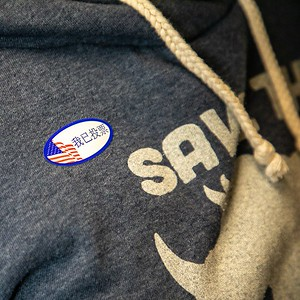 """Voter Elaine Lander asked for a Chinese """"I Voted"""" sticker at the Sierra 2 Vote Center during the presidential primary on March 3, 2020. (Photo by Joan Cusick)"""