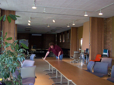 Adam is moving the tables and chairs so everyone will have a place to sit when they come to eat.