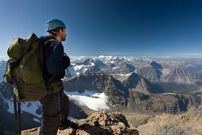 Young male mountaineer standing on summit of mountain in the Rocky Mountains of Canada.