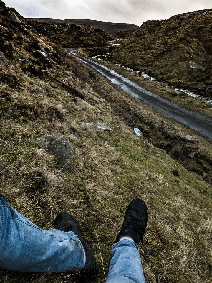 A mans view of a winding mountain road.