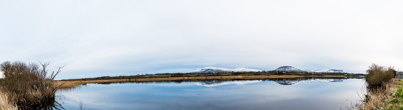 Snowy Benwisken and Benbulben Mountain with a still lake in the foreground and a perfect reflection.