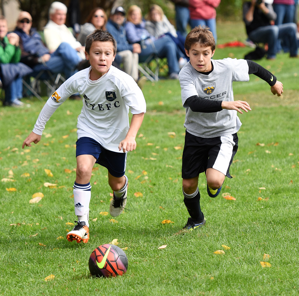 STAN HUDY - SHUDY@DIGITALFIRSTMEDIA.COMA New York Elite FC player and a Clifton Park Soccer player race for a 50-50 ball during Sunday's competition at the Clifton Park Fall Soccer Classic on the Clifton Common, Oct. 9, 2016.
