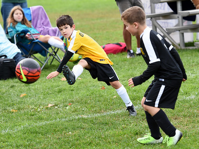 STAN HUDY - SHUDY@DIGITALFIRSTMEDIA.COM A Clifton Park Youth Soccer Club player kicks the ball past a defender during a U8 co-ed game Sunday, Oct. 8 at the Clifton Common during the 2016 Clifton Park Fall Soccer Classic.