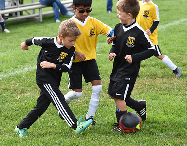 STAN HUDY - SHUDY@DIGITALFIRSTMEDIA.COM A Clifton Park Youth Soccer Club player kicks the ball away from a defender during a U8 co-ed game Sunday, Oct. 8 at the Clifton Common during the 2016 Clifton Park Fall Soccer Classic.