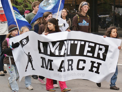 "Young children carry large ""I Matter March"" banner, other protesters with earth flags behind them."