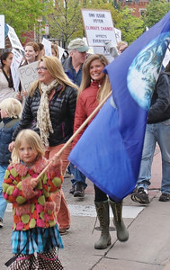 Young girl carries earth flag, other climate cahnge marchers behind her.