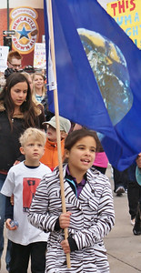 Young girl carries earth flag, young boy behind her looks up at flag, other marchers behind them.