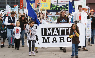 "Young boy with torch and young girl with earth flag lead march, others carry large ""I Matter March"" banner behind them."