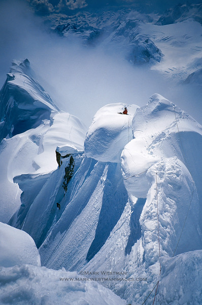 "Forrest Murphy belays from atop a massive cornice on Mount Hunter's south ridge route. In the foreground is the ""Happy Cowboy"" traverse, named for the need to straddle the unstable ridge, as one would a horse, for progr"