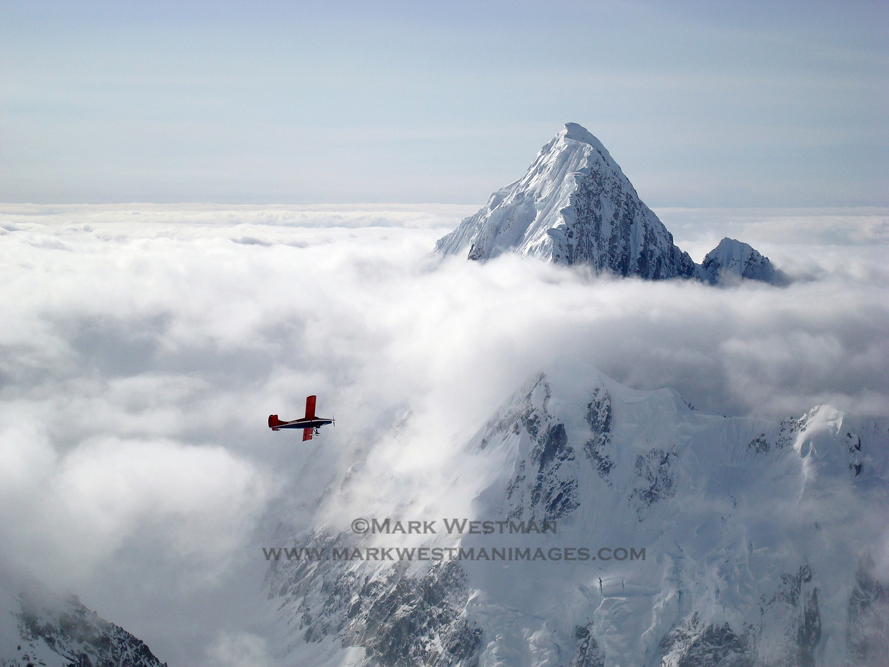 Paul Roderick flying his DeHavilland Otter in front of Mount Huntington. I took this photograph from 11,200 feet during an ascent of Denali's Isis Face. Paul is my brother in law and the owner of Talkeetna Air Taxi,  and was flying by to see how we were doing.<br /> <br /> This photo was featured as a double page spread in the Table of Contents page in Alpinist Magazine, issue #29.