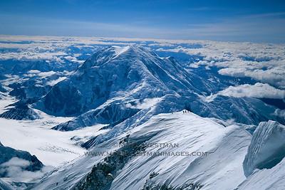 Climbers on Denali's summit ridge, with Mount Foraker beyond.