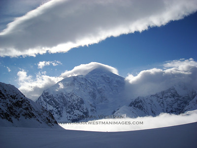 Afternoon clouds and fog surround Mount Foraker (17,400'), standing tall above the 7,200' Kahiltna basecamp on Denali.