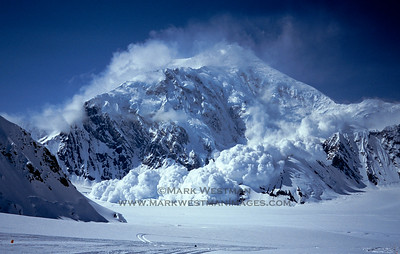A colossal ice avalanche falls from Mount Foraker's 3000 meter tall east face to the Kahiltna Glacier.