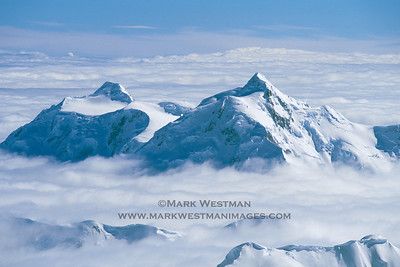 Mount Hunter's south and north summits stand above a cloud sea.